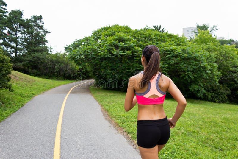 Jovem mulher que corre na fuga movimentando-se fotografia de stock