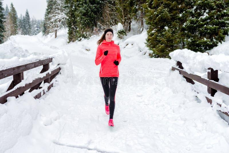 Jovem mulher que corre na neve nas montanhas do inverno que vestem luvas mornas da roupa no tempo da neve imagens de stock royalty free