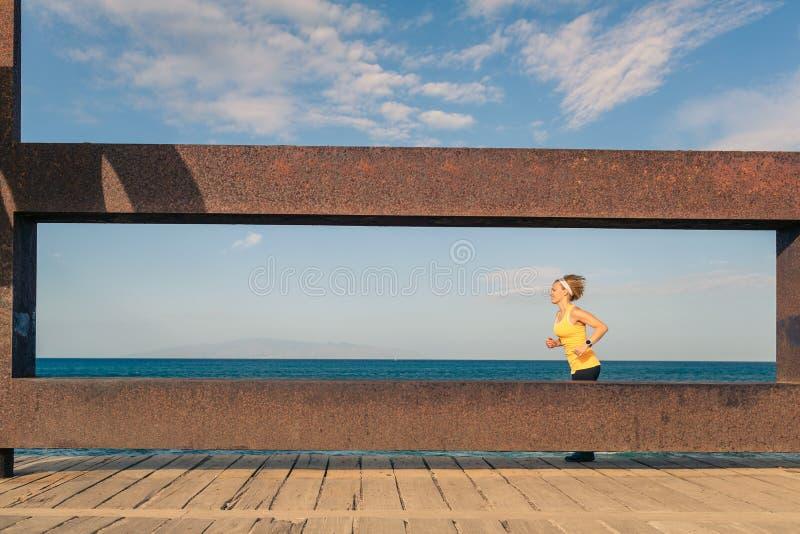 Jovem mulher que corre nas montanhas no dia de verão ensolarado imagem de stock