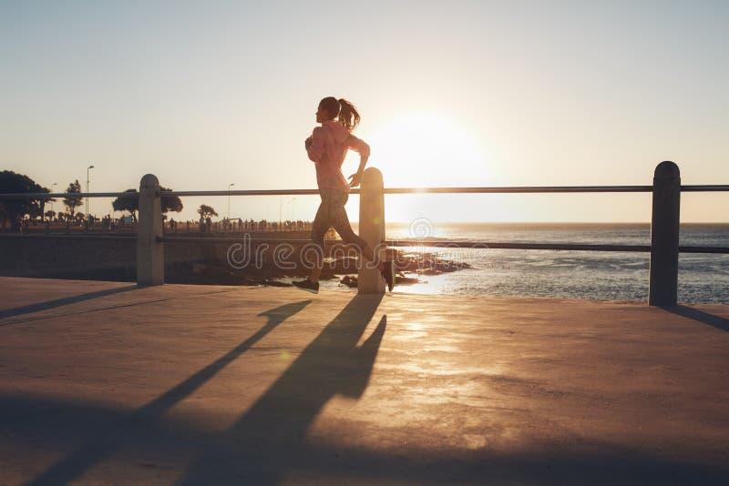 Jovem mulher que corre no passeio do beira-mar imagens de stock royalty free