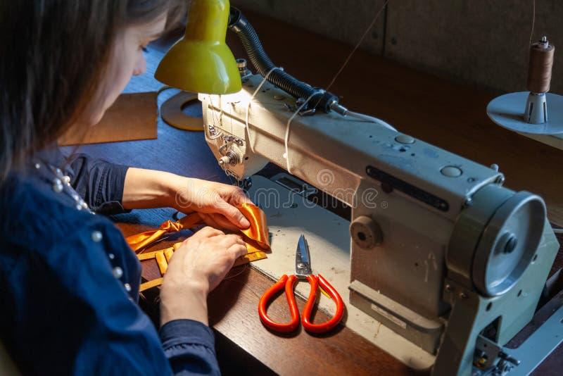 Jovem mulher que costura na máquina de costura foto de stock