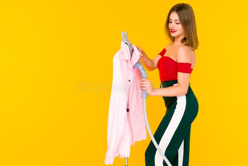Jovem mulher que cozinha a camisa cor-de-rosa em seco-líquidos de limpeza imagem de stock royalty free