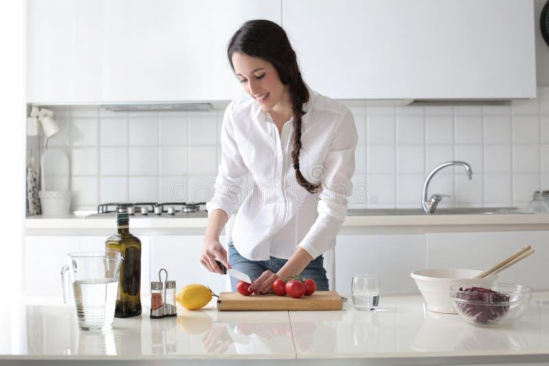 Jovem mulher que cozinha em sua cozinha imagens de stock royalty free