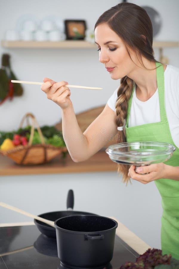 Jovem mulher que cozinha em uma cozinha Sopa do gosto da dona de casa pela colher de madeira foto de stock royalty free