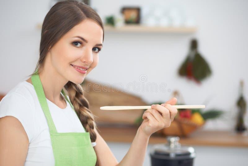 Jovem mulher que cozinha em uma cozinha Sopa do gosto da dona de casa pela colher de madeira foto de stock