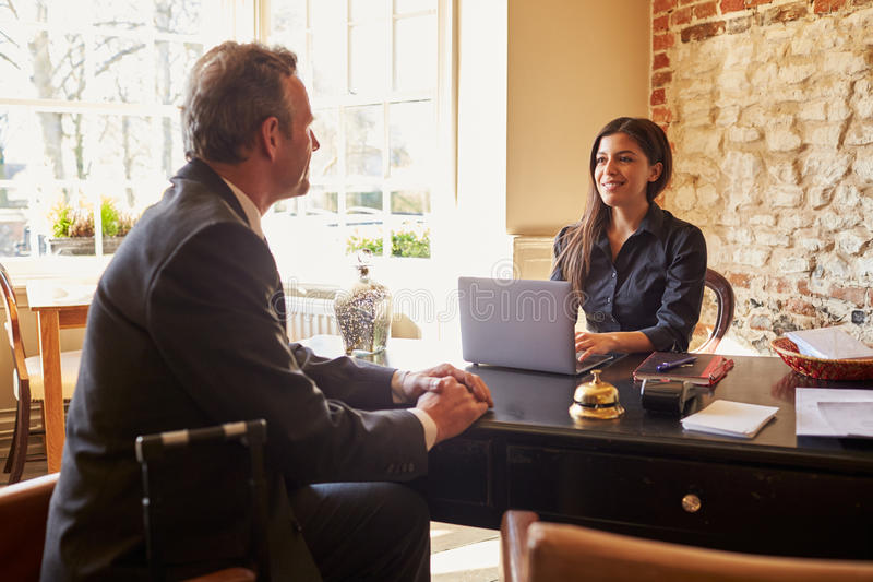 Jovem mulher que cumprimenta um convidado na mesa de registro de um hotel foto de stock royalty free