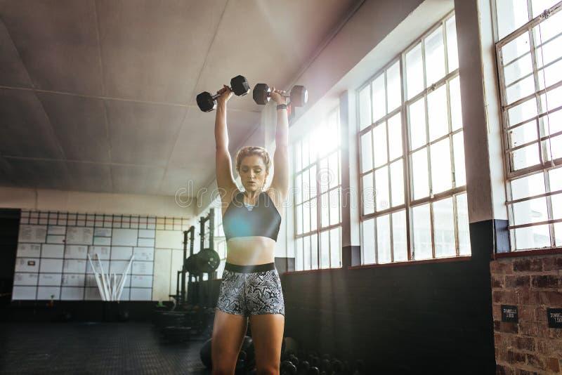 Jovem mulher que dá certo no ginásio usando pesos foto de stock royalty free