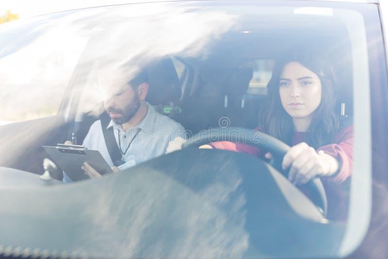 Jovem mulher que dá o teste da condução de carro fotografia de stock