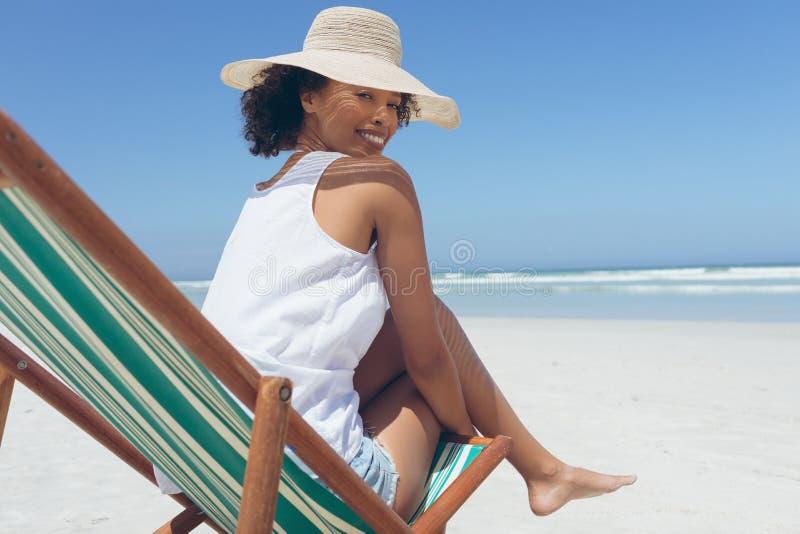 Jovem mulher que dá a pose ao sentar-se no vadio do sol na praia imagem de stock royalty free