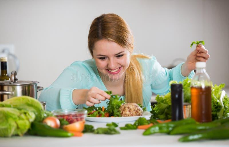 Jovem mulher que decora a salada com as ervas na cozinha fotografia de stock royalty free