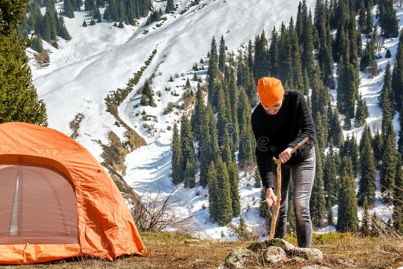 Jovem mulher que desbasta a madeira com um machado perto de uma barraca do turista nas montanhas contra um fundo da floresta cobe imagens de stock royalty free