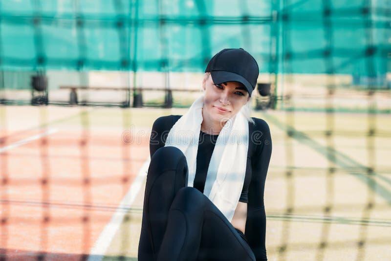 Jovem mulher que descansa após ter feito esportes em um campo de tênis Aptid?o e conceito saud?vel do estilo de vida fotos de stock