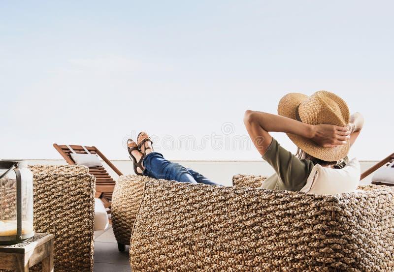 Jovem mulher que descansa no terraço do hotel Férias e conceito do divertimento do verão Menina bonita que aprecia a vida imagens de stock royalty free