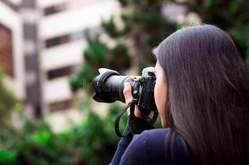 Jovem mulher que desengaça e que toma imagens com sua câmera, na parte externa com um fundo do escritório foto de stock