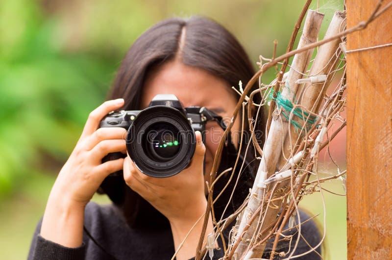 Jovem mulher que desengaça e que toma imagens com sua câmera, na parte externa imagens de stock