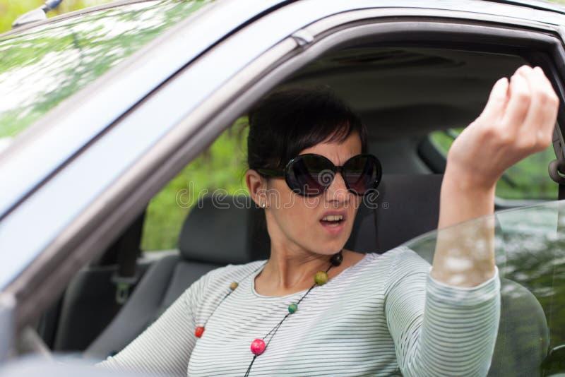 Jovem mulher que discute do carro imagem de stock