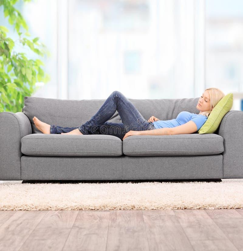 Jovem mulher que dorme em um sofá moderno em casa imagens de stock royalty free