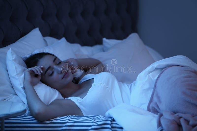Jovem mulher que dorme na cama na noite imagem de stock