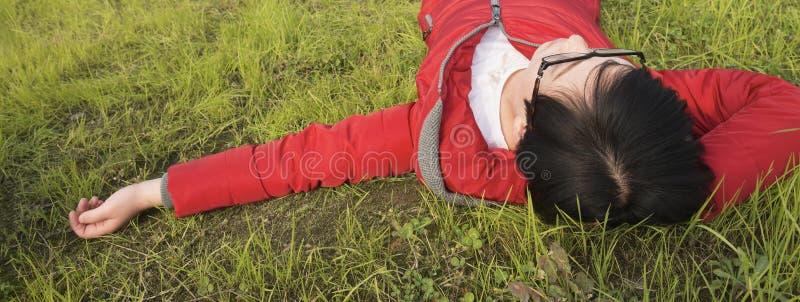 Jovem mulher que dorme no gramado imagem de stock royalty free