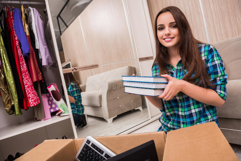 A jovem mulher que embala pertences pessoais imagens de stock
