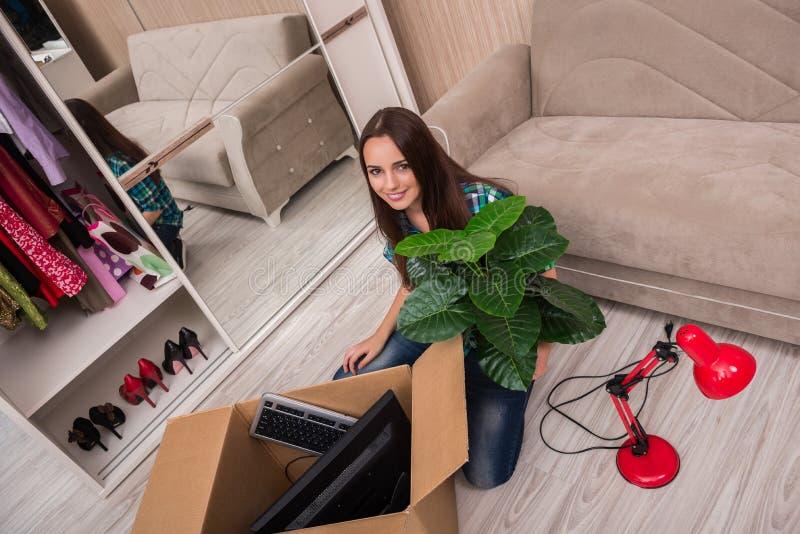 A jovem mulher que embala pertences pessoais foto de stock
