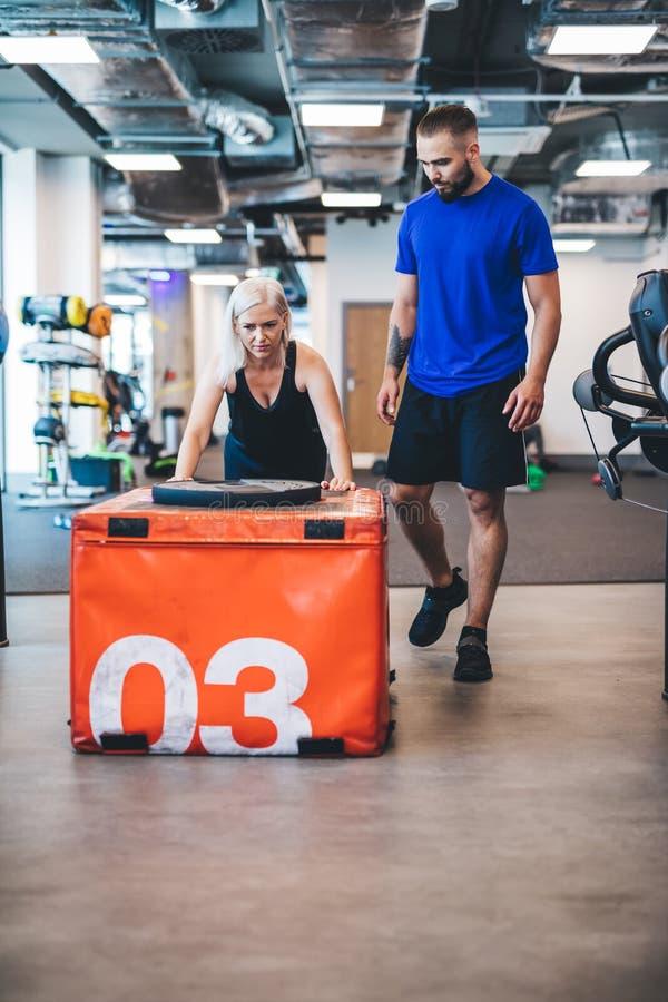 Jovem mulher que empurra o peso no gym imagem de stock royalty free