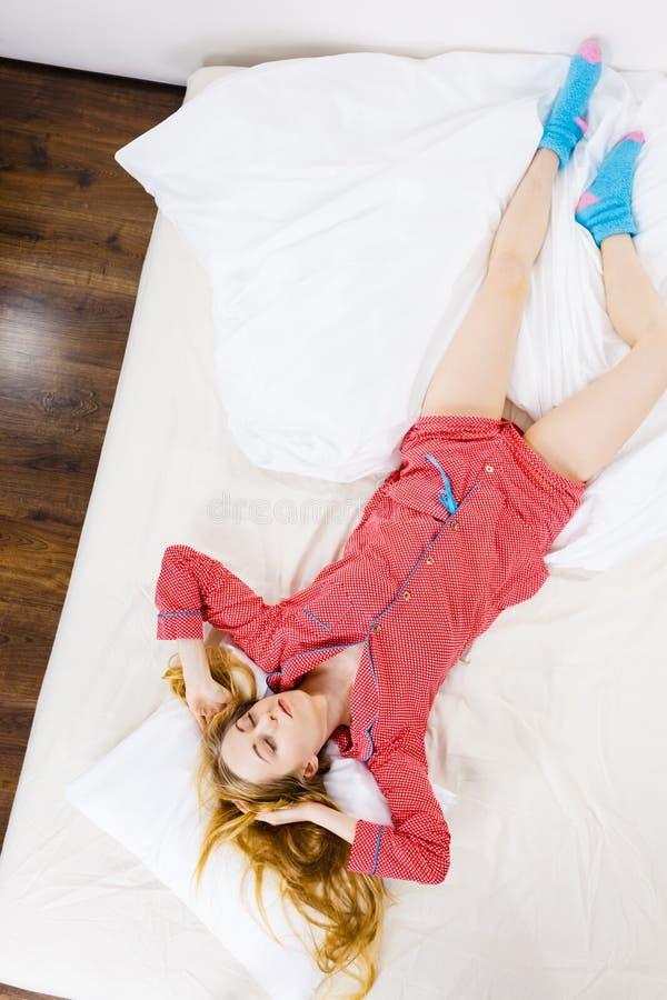 Jovem mulher que encontra-se em pijamas vestindo da cama foto de stock royalty free