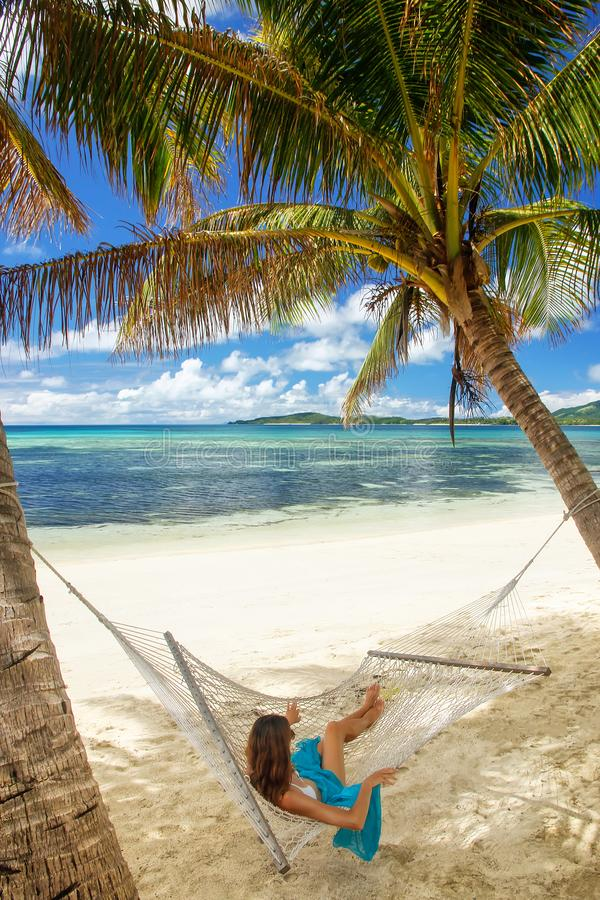 Jovem mulher que encontra-se em uma rede em uma praia tropical imagens de stock royalty free