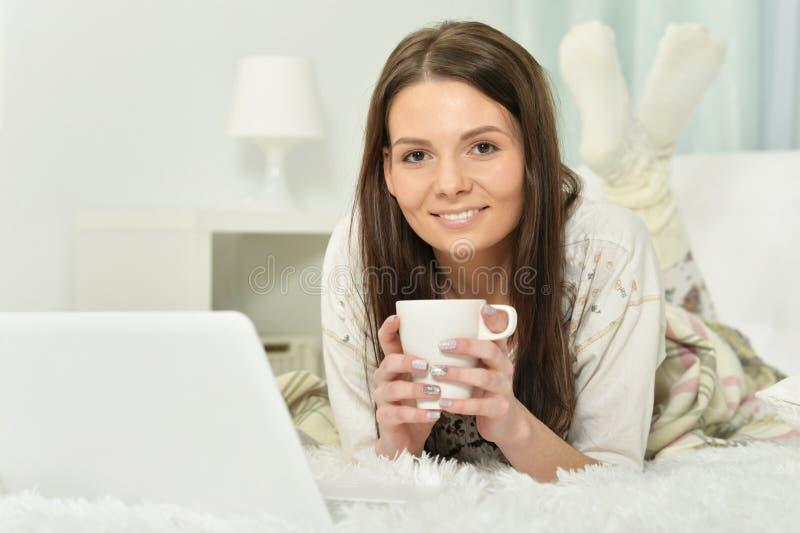 Jovem mulher que encontra-se na cama com x?cara de caf? fotos de stock royalty free