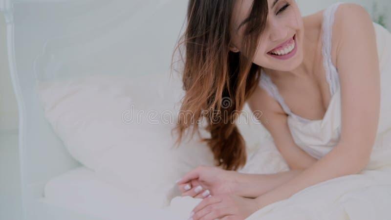 Jovem mulher que encontra-se na cama e no riso Menina moreno feliz que acorda e que tem o divertimento na manhã em casa fotos de stock
