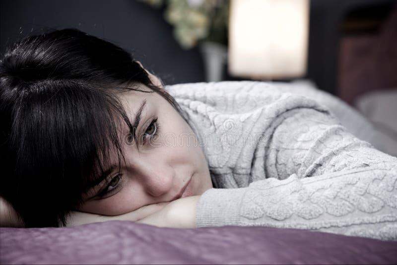 Jovem mulher que encontra-se na cama que pensa sobre amor perdido infeliz imagem de stock royalty free
