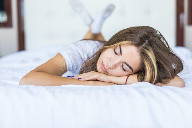 Jovem mulher que encontra-se na extremidade da cama que olha para a frente ao sorrir e sua cabeça que descansa em ambas suas mãos imagens de stock