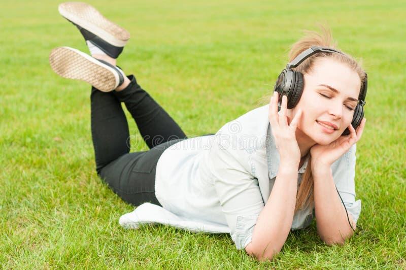 A jovem mulher que encontra-se na grama e escuta a música foto de stock royalty free