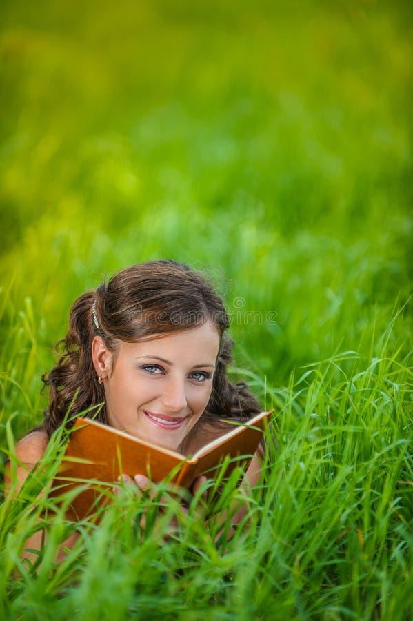 Jovem mulher que encontra-se na grama e no livro de leitura imagens de stock