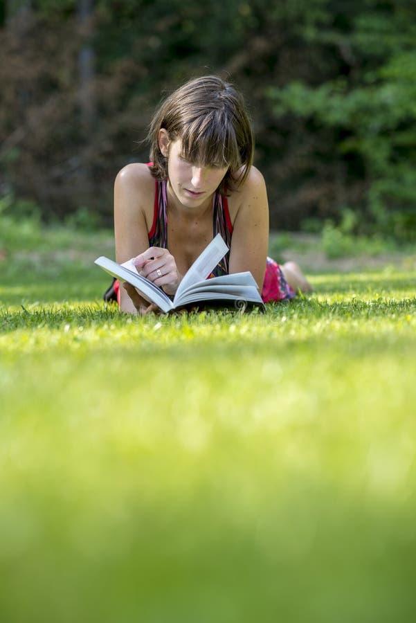 Jovem mulher que encontra-se na grama verde que lê um livro fotografia de stock