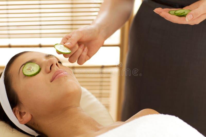 Jovem mulher que encontra-se na tabela da massagem com a fatia do pepino que está sendo colocada sobre o olho fotos de stock royalty free