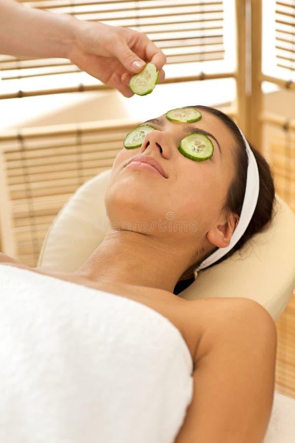 Jovem mulher que encontra-se na tabela da massagem com a fatia do pepino que está sendo colocada sobre o olho foto de stock royalty free