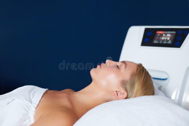 Jovem mulher que encontra-se na tabela da massagem na clínica dos termas imagens de stock royalty free