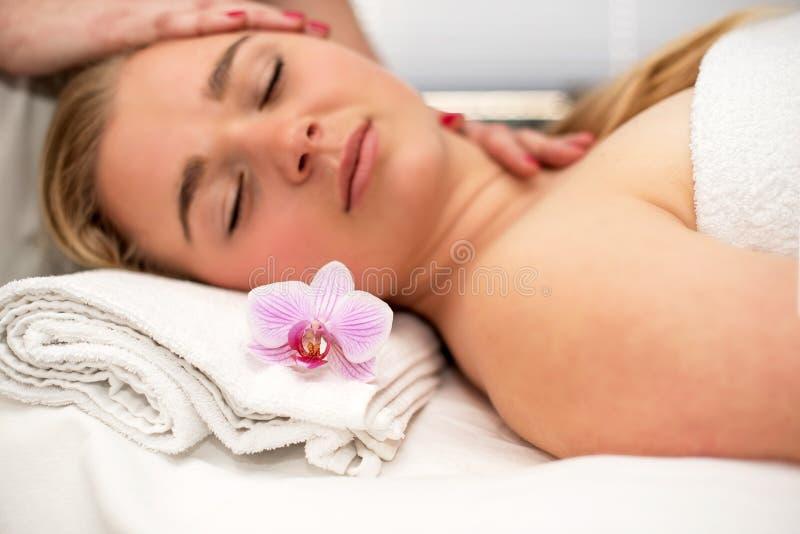 Jovem mulher que encontra-se na tabela da massagem que recebe a massagem de cara beaut imagens de stock royalty free