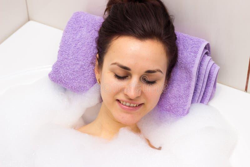 Jovem mulher que encontra-se no banho imagens de stock