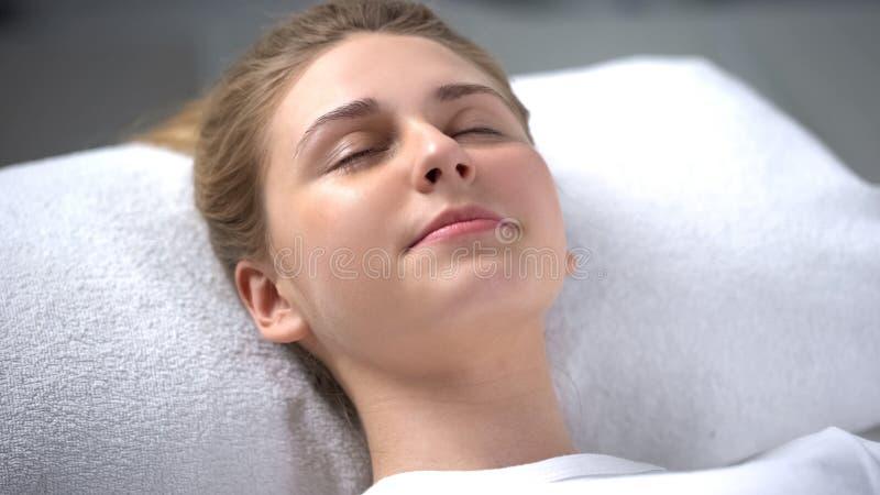 Jovem mulher que encontra-se para baixo e que relaxa no salão de beleza do cosmetologist, cuidados com a pele foto de stock