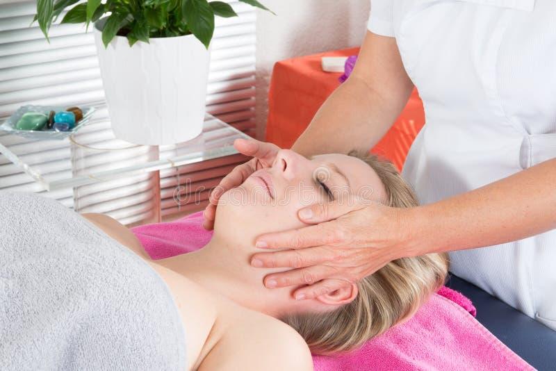 jovem mulher que encontra-se sobre parte traseira quando terapeuta da massagem que faz massagens sua cara em uma sala de estar de imagens de stock royalty free