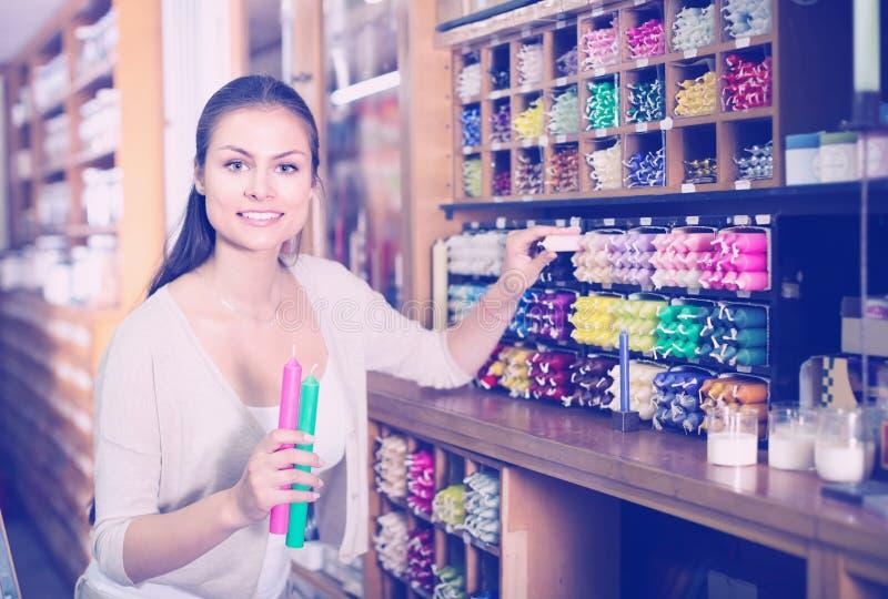 Jovem mulher que escolhe velas na loja de ofício fotos de stock