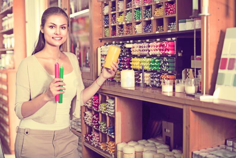 Jovem mulher que escolhe velas na loja de ofício imagem de stock