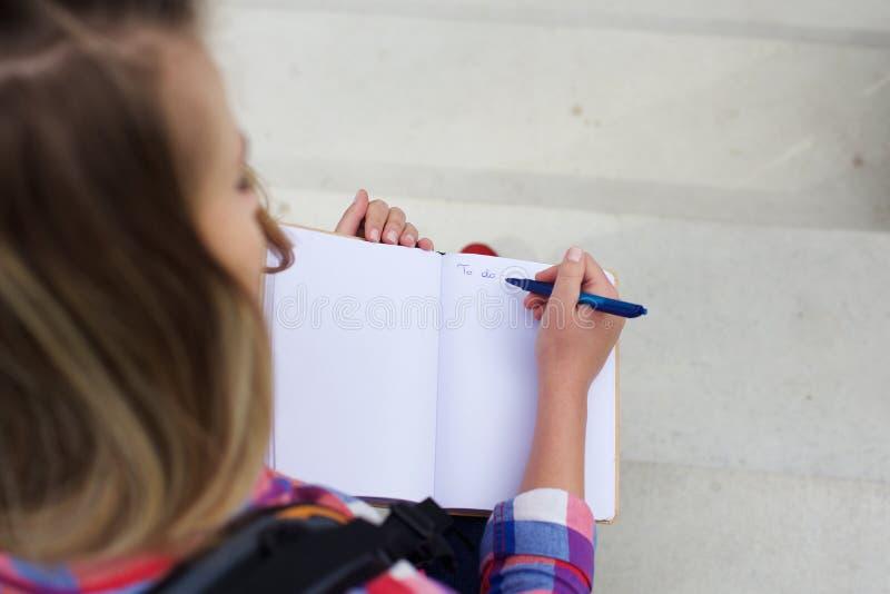 Jovem mulher que escreve a para fazer a lista no livro foto de stock