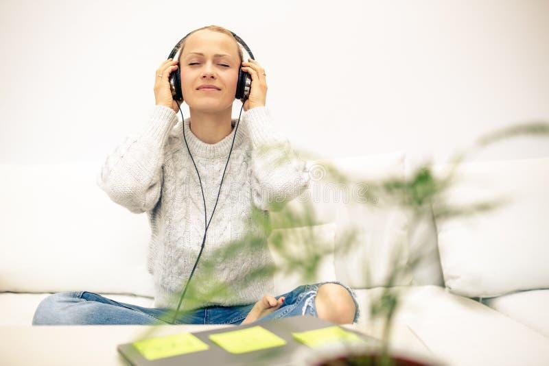 Jovem mulher que escuta a música do telefone esperto usando fones de ouvido imagens de stock royalty free