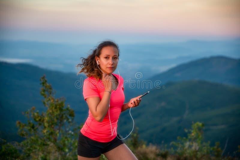 Jovem mulher que escuta a música durante a fuga que corre nas montanhas foto de stock