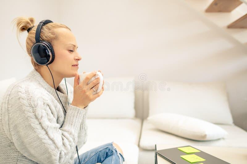 Jovem mulher que escuta a música e que aprecia a xícara de café imagens de stock royalty free