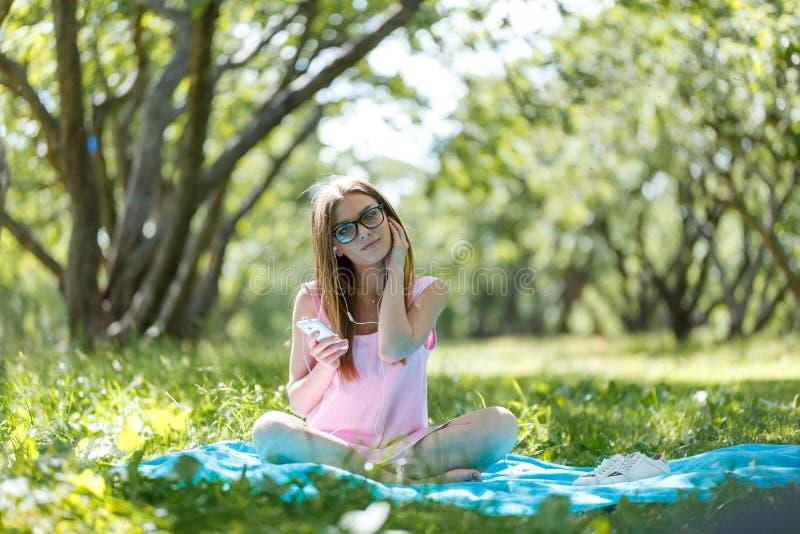 Jovem mulher que escuta a música em auscultadores Senta-se na grama no parque, descansando aprecia a natureza foto de stock royalty free