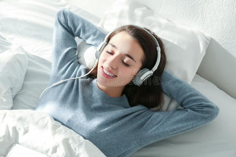 Jovem mulher que escuta a música nos fones de ouvido imagens de stock